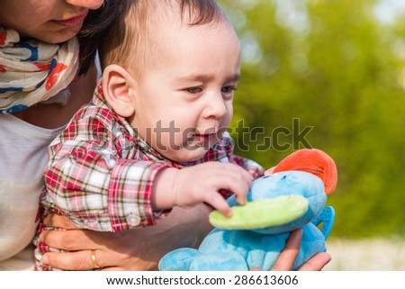 Cute 6 months old baby with Light brown hair in red checkered shirt and beige pants is touching toys while embraced by his mother