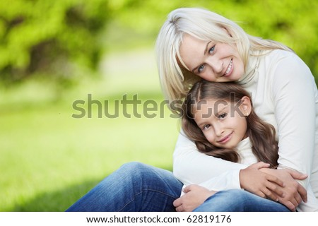 Cute mother and daughter outdoors - stock photo