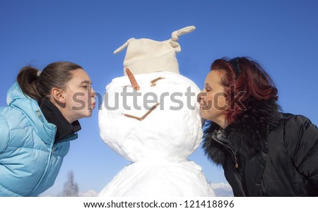 Cute mother and her daughter kissing snowman on a sunny winter day - stock photo
