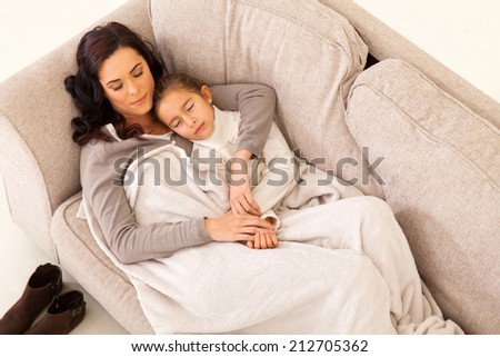 cute mother and her little girl sleeping on the couch - stock photo