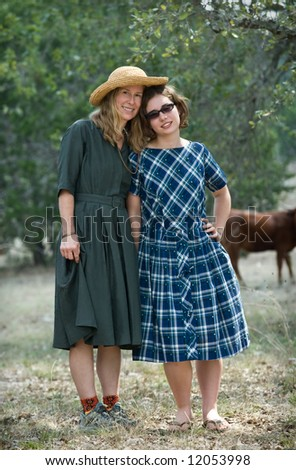 Cute mother and teenage daughter arm in arm together, outdoors, sunny setting; wearing vintage dresses