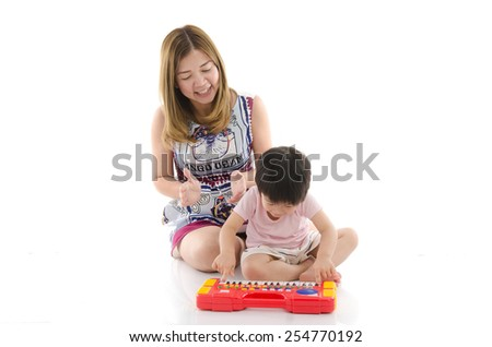 Cute mother teach her son kid to play electrical toy piano on white background isolated - stock photo