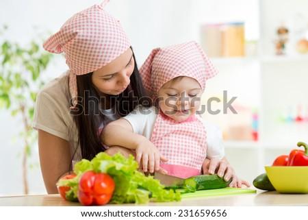 cute mother teaches daughter knife cutting cucumber - stock photo
