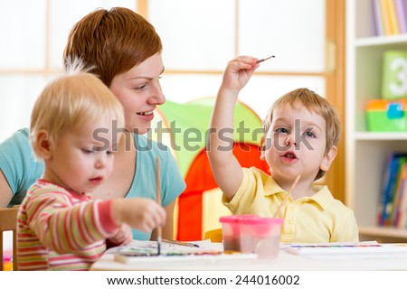 cute mother teaching her kids to paint at home - stock photo