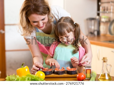 Cute mother with child daughter preparing fish in kitchen - stock photo