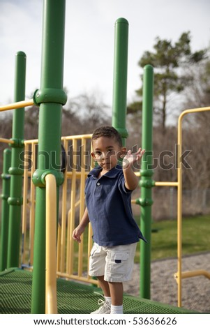 Cute multi-racial boy at the park waves at the camera - stock photo