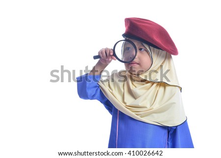 Cute muslim young girl trying to use magnifying glass
