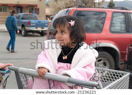 Cute Native American girl sitting in a shopping cart ready for grocery store run with her mother - stock photo