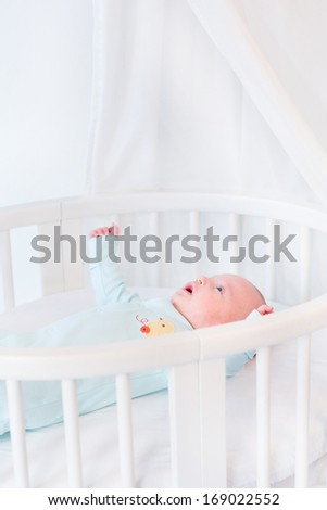 Cute newborn baby boy in a white round bed with canopy - stock photo