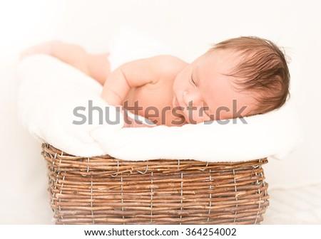 Cute newborn baby boy sleeping in old wicker basket covered by blanket - stock photo