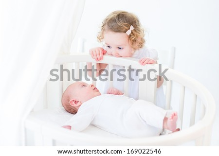 Cute newborn baby boy watching his toddler sister standing at his white round crib in a sunny bedroom - stock photo