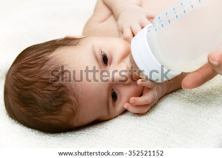 Cute newborn baby eating from the plastic bottle
