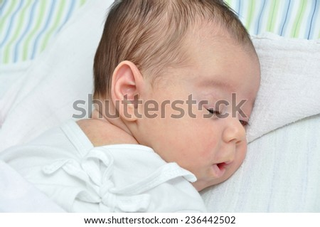 Cute newborn baby girl lying in bed and waking up - stock photo