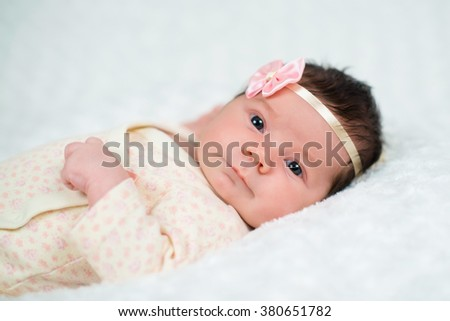 Cute newborn baby girl with pink bow - stock photo