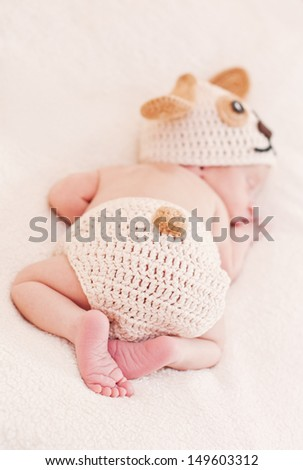 cute newborn baby sleeps in a knitted hat dogs focus on legs - stock photo