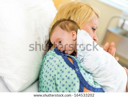 Cute newborn babygirl resting on mother's shoulder in hospital - stock photo