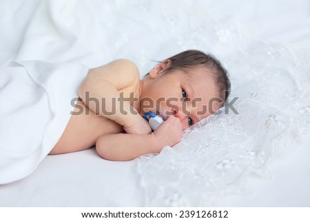 Cute newborn boy girl nursing baby's dummy on background of white lace. Soft image, focus on hands, dummy and nose.  - stock photo