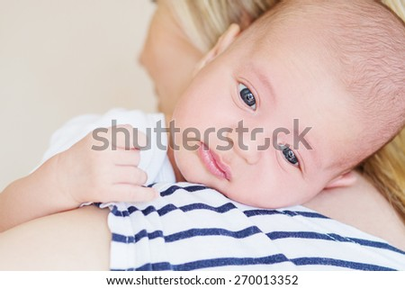 cute newborn boy on the shoulder of mother - stock photo