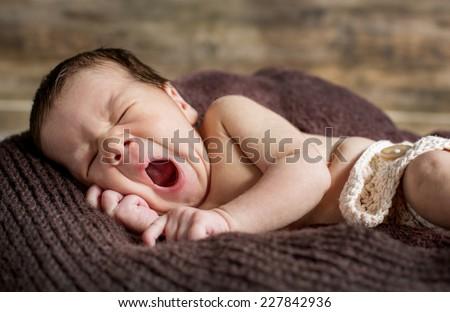 cute newborn yawns lying on brown blanket - stock photo