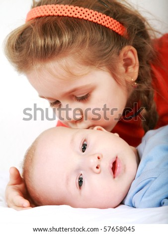 Cute older sister giving a kiss to her brother - stock photo