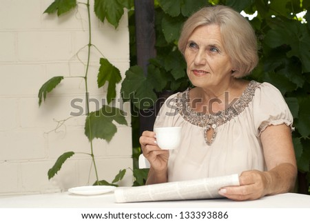 Cute older woman sitting at a table at home on the veranda