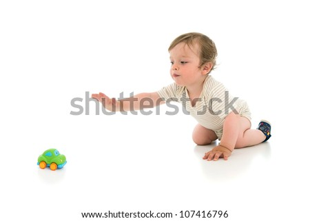 Cute one year old boy reaching for the toy, isolated on white background