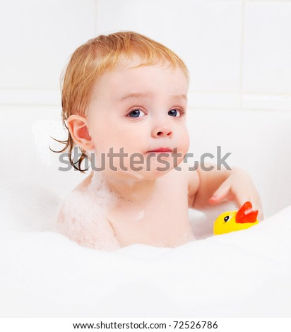 cute one year old boy taking a  bath with foam and playing with a toy duck