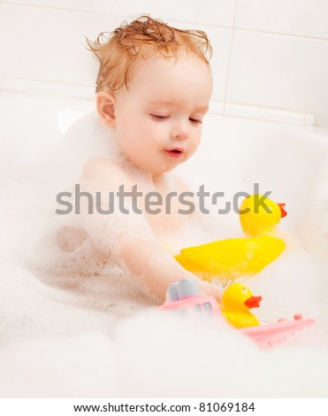 cute one year old boy taking a  bath with foam and playing with toys