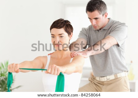 Cute Patient doing some exercises under supervision in a room - stock photo