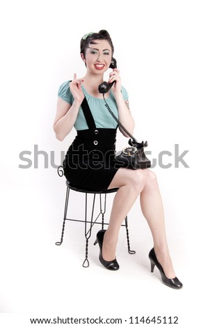 Cute pin up girl talking on an antique telephone - stock photo