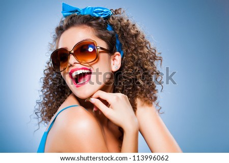 cute pin up girl with perfect teeth smiling, curly hair and sunglasses on blue background - stock photo
