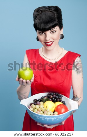Cute pinup model holding a bowl of fruit - stock photo