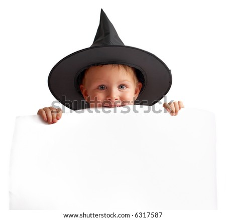 Cute playful boy in witch hat holds white banner.
