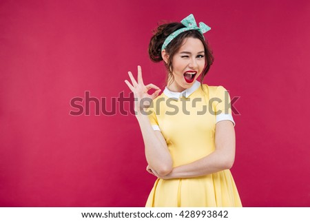 Cute playful pinup girl in yellow dress winking and showing ok sign over pink background - stock photo
