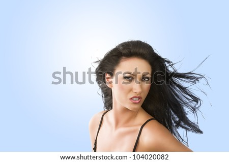 cute portrait of sensual brunette playing with hair. She looks in to the lens with attractive expression.