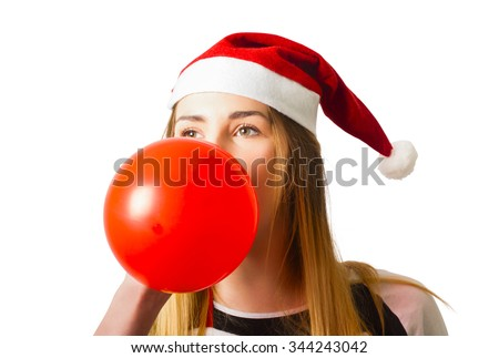 Cute portrait on the head of adorable blond girl in santa hat blowing up a red balloon in preparation for celebrations. Christmas party planner