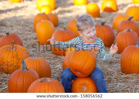 cute positive boy having fun and being silly at the pumpkin patch