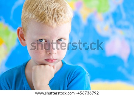Cute preschool boy dreaming in fron of  world map - stock photo