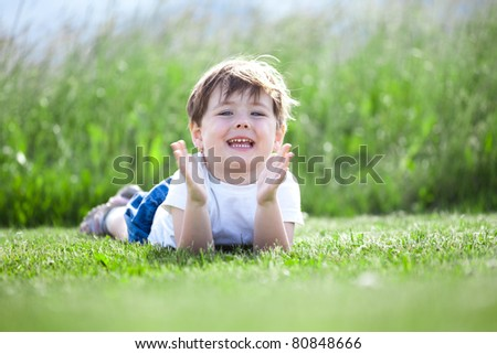 Cute preschool girl lying on green grass with field in background.