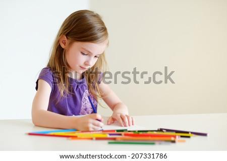 Cute preschooler girl drawing a picture with colorful pencils - stock photo