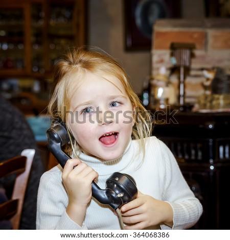Cute preschooler girl talking by old vintage retro telephon, closeup portrait - stock photo