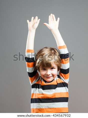 Cute Preschooler having fun in orange black striped shirt, Holding up his Arms, Celebrating - stock photo