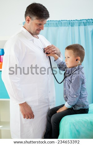 Cute preschooler using stethoscope at pediatrician's office - stock photo