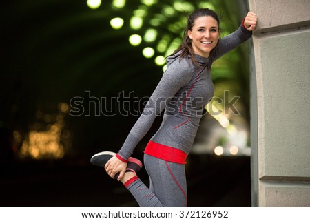 Cute pretty fun athlete stretching smiling urban fitness exercise stretch routine - stock photo