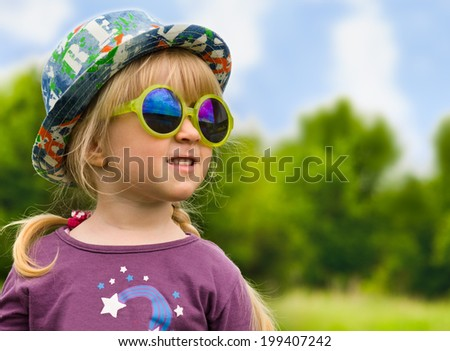 Cute pretty little girl in trendy summer fashion wearing big yellow sunglasses and a colourful sunhat with her blond hair in pigtails standing in a rural field