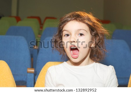 cute pretty little girl shouting in the cinema hall - stock photo
