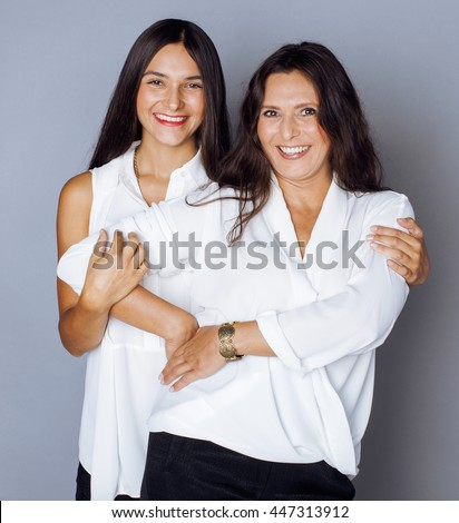 cute pretty teen daughter with mature mother hugging, fashion style brunette - stock photo
