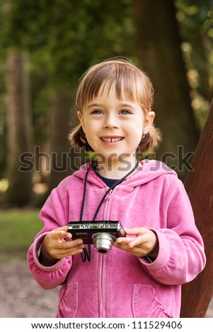 Cute pretty young girl taking pictures with a digital camera - stock photo