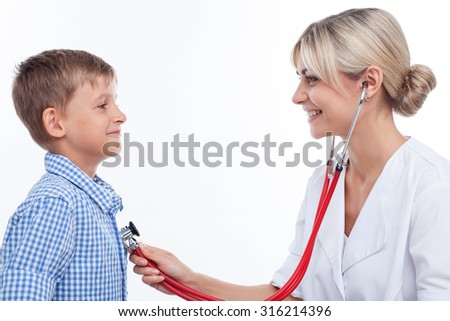 Cute professional doctor is holding a stethoscope and touching it to chest of child. She is listening heartbeat of boy attentively.  They are smiling. Isolated - stock photo