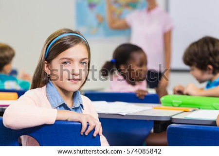 Cute pupil looking at camera during lesson in classroom
